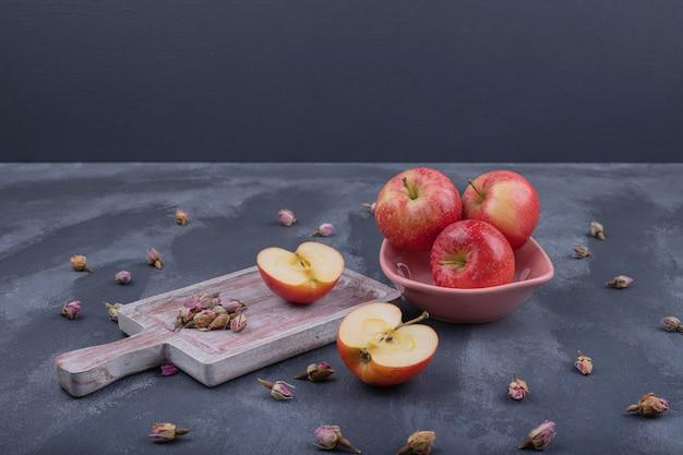 Verschillende appels op plaat met verdorde roos op donker. Gratis Foto