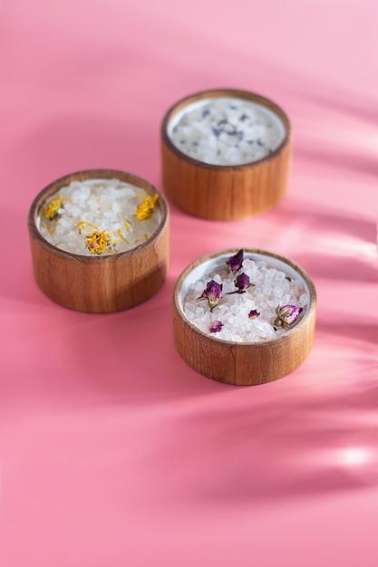 Verschillende badzout in een houten plaat op een roze achtergrond. zonnestralen. het concept van spa-behandelingen, huidverzorging. etherische oliën en gedroogde bloemen roos, lavendel. Premium Foto