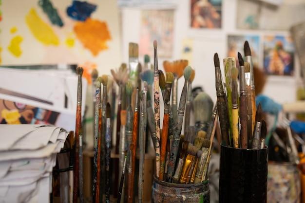 Verschillende borstels. verschillende denk- en dikke verfborstels staan in werkplaats van bekende kunstenaars Premium Foto