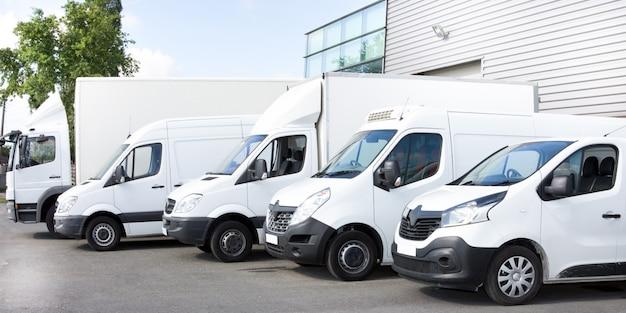 Verschillende busjes en vrachtwagens geparkeerd op parkeerplaats te huur Premium Foto