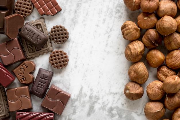 Verschillende chocolade blokken en hazelnoten op witte achtergrond Gratis Foto