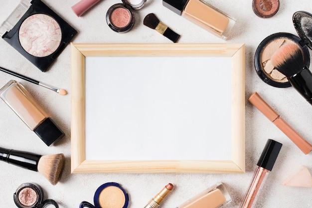 Verschillende cosmetica en lege frame verspreid over lichte achtergrond Gratis Foto