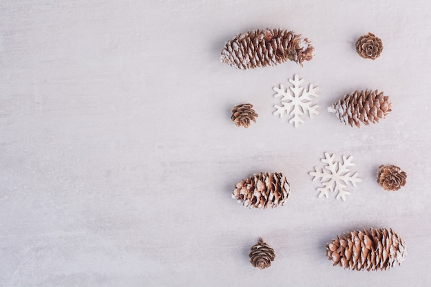 Verschillende dennenappels en sneeuwvlokken op wit oppervlak Gratis Foto