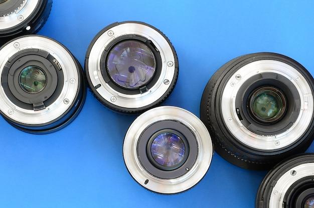 Verschillende fotografische lenzen liggen op een helderblauwe achtergrond. ruimte voor tekst Premium Foto
