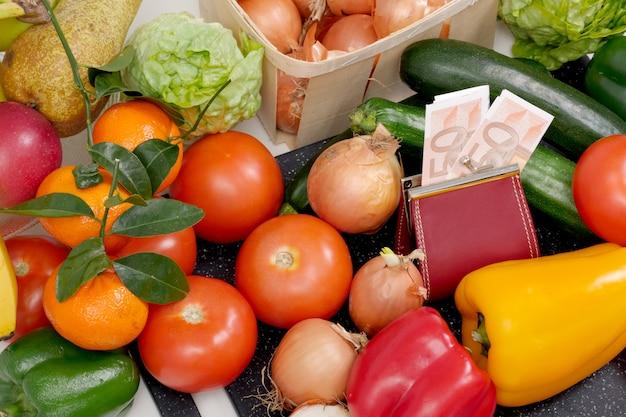 Verschillende groenten en seizoensfruit met contant geld Premium Foto