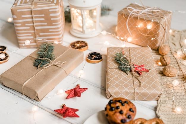 Verschillende ingepakte geschenken onder decoratieve rode sterren, walnoten, sprankelende slingers, schijfjes citroen en koekjes op witte tafel Premium Foto