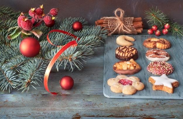 Verschillende koekjes met kaneelstokjes, kerstboomtakjes, kerstballen en bessen Premium Foto