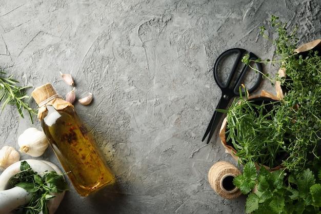 Verschillende kruiden, olie en mortel op grijze achtergrond, ruimte voor tekst Premium Foto