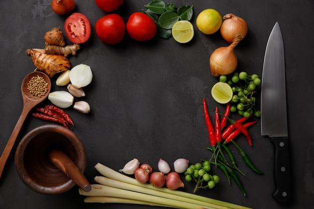 Verschillende kruiden, specerijen en ingrediënten op donker. bovenaanzicht Premium Foto