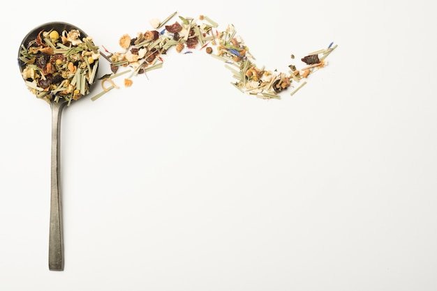 Verschillende kruiden voor het maken van gezonde thee in pollepel op witte achtergrond Gratis Foto
