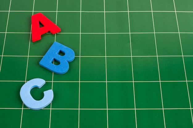 Verschillende letters liggen op het groene oppervlak van het bord Premium Foto