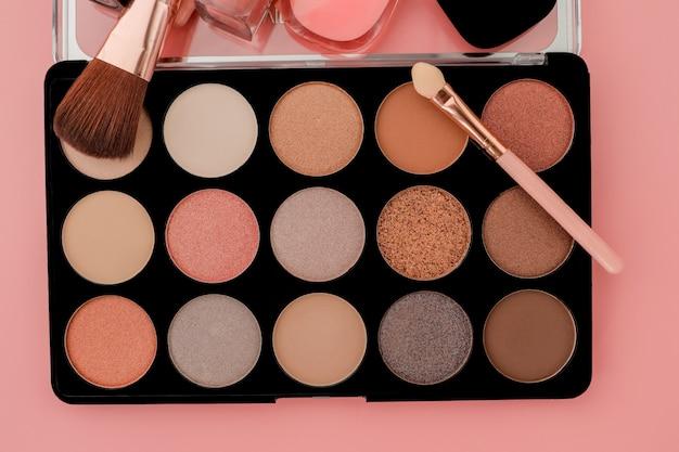 Verschillende make-up producten op roze oppervlak met copyspace Premium Foto