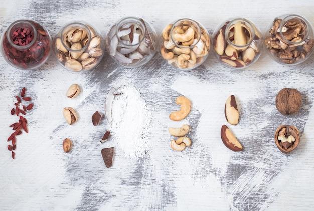 Verschillende noten in kleine potten op een lichte houten achtergrond, een concept van gezonde voeding Gratis Foto