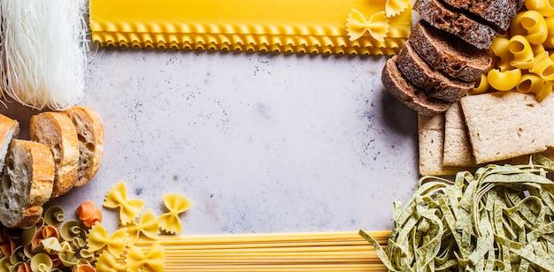 Verschillende pasta achtergrond. brood en verschillende pasta op grijs-blauwe achtergrond, kopie ruimte, bovenaanzicht. Premium Foto