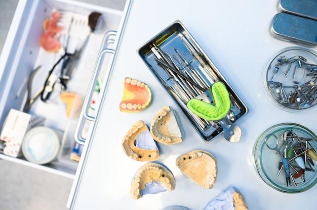 Verschillende professionele tandheelkundige apparatuur, instrumenten en instrumenten in een tandartsen stomatologie kantoor kliniek op een witte achtergrond. gegoten siliconen kaak. Premium Foto