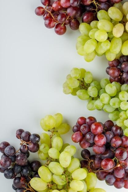 Verschillende rijpe druiven op een wit. Gratis Foto