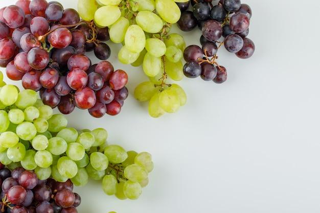 Verschillende rijpe druiven plat lag op een wit Gratis Foto