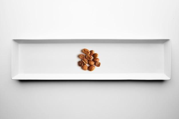Verschillende soorten artisanale professionele roosterende koffie geïsoleerd op een witte plaat, bovenaanzicht Gratis Foto