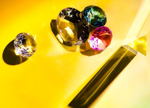 Verschillende soorten diamanten op gele achtergrond Gratis Foto