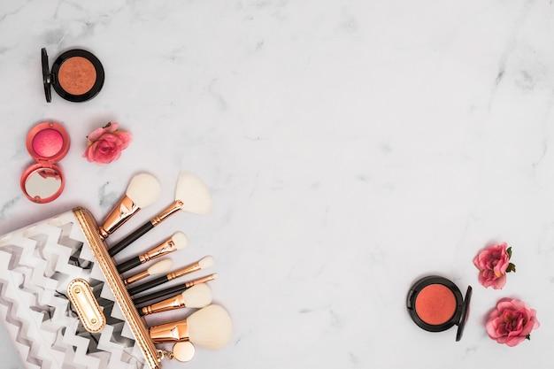 Verschillende soorten make-upborstels in de zak met compact gezichtspoeder en roze bloemen op witte achtergrond Gratis Foto