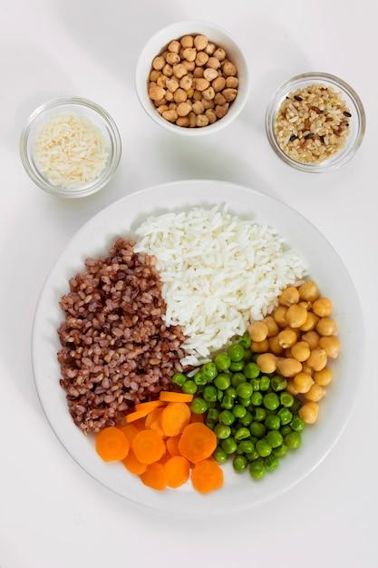 Verschillende soorten pap met groenten op plaat met rijstkommen Gratis Foto