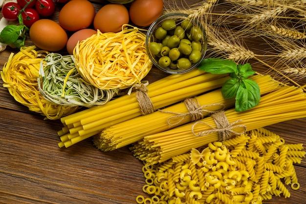Verschillende soorten pasta, bukatini en fettuccine en girandole op tafel met basilicum en olijven, ook met kippeneieren Premium Foto