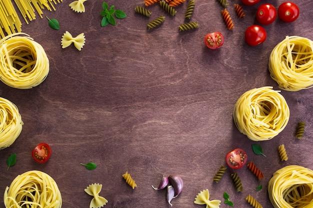 Verschillende soorten pasta op een houten achtergrond Premium Foto