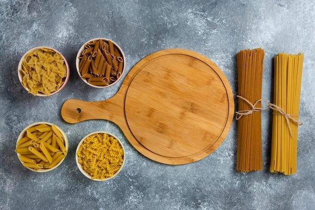 Verschillende soorten rauwe spaghetti met houten plank. Gratis Foto