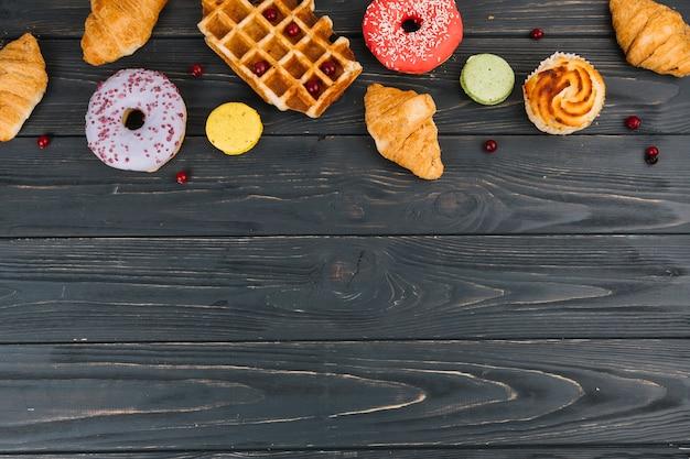 Verschillende soorten snoep gebakken items op houten tafel Gratis Foto