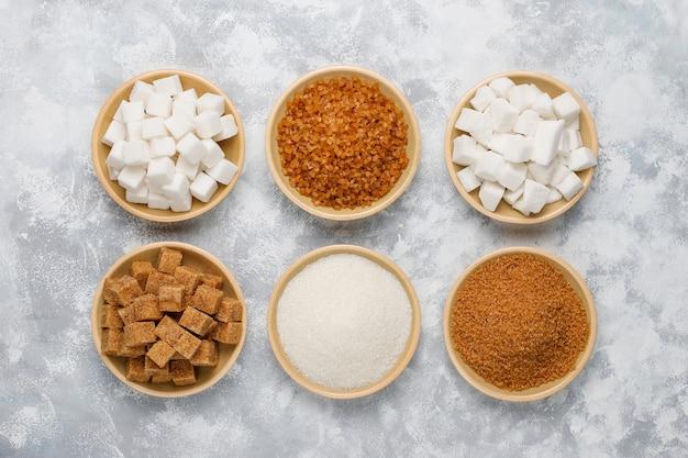 Verschillende soorten suiker, bruine suiker en wit op beton, bovenaanzicht Gratis Foto