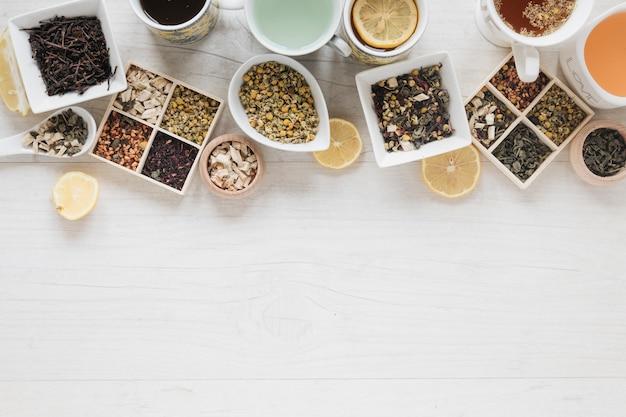 Verschillende soorten thee met kruiden en droge theebladen op bureau Gratis Foto