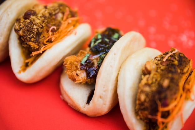 Verschillende soorten traditionele gua bao van taiwan op rode achtergrond Gratis Foto