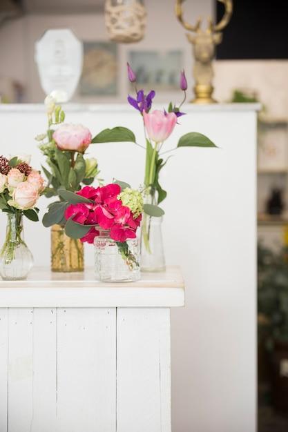 Verschillende soorten vazen met kleurrijke bloemen op tafel in de winkel van de bloemist Gratis Foto