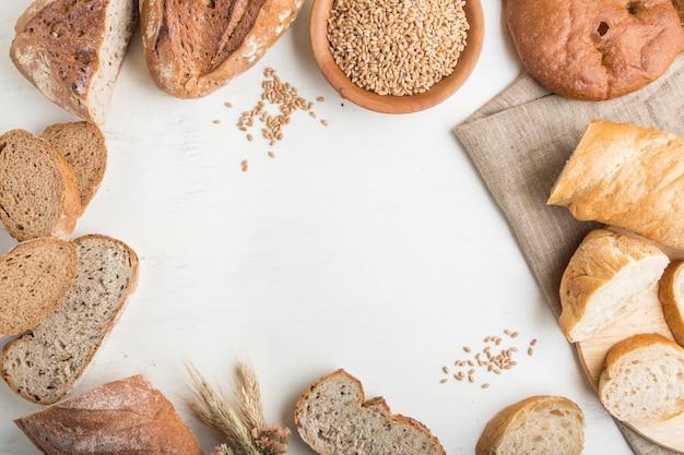 Verschillende soorten vers gebakken brood in een vorm van frame op een witte houten muur. bovenaanzicht, kopie ruimte. Premium Foto