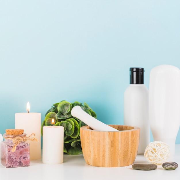 Verschillende spa-producten met verlicht; kaarsen; mortier en stamper op wit tafelblad Gratis Foto