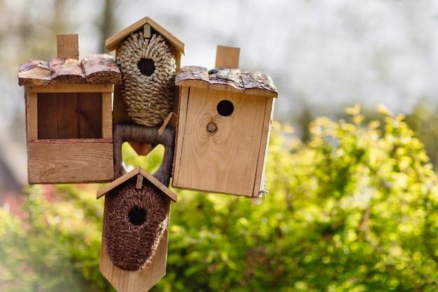 Verschillende vogelhuisjes en een vogelvoeder op een stokje. Premium Foto