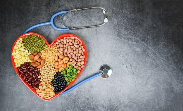 Verschillende volle granen bonen en peulvruchten zaden linzen en noten kleurrijk op rood hart - collage verschillende bonen mix erwten landbouw van natuurlijke gezonde voeding voor het koken van ingrediënten Premium Foto