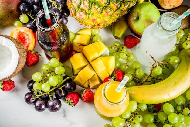 Verschillende vruchtensappen smoothies concept zomer vitaminen dieet met tropische vruchten en bessen op een lichte achtergrond Premium Foto