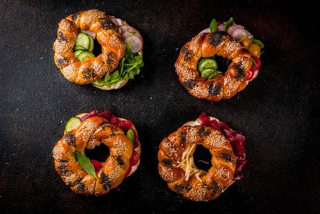 Verschillende zelfgemaakte bagelsandwiches met sesam- en maanzaad, roomkaas, ham, radijs, rucola, kerstomaatjes, komkommers, donker betonnen oppervlak hierboven Premium Foto
