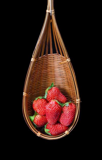 Verse aardbei in een houten mand die op zwarte achtergrond wordt geïsoleerd Premium Foto