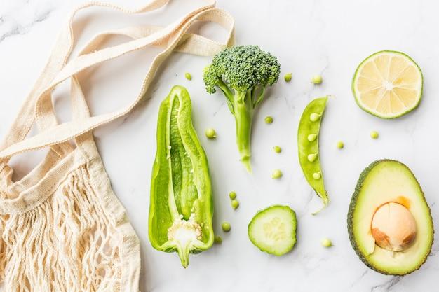 Verse avocado, limoen, broccoli, groene erwten, komkommer, groene paprika, touwzak. Premium Foto