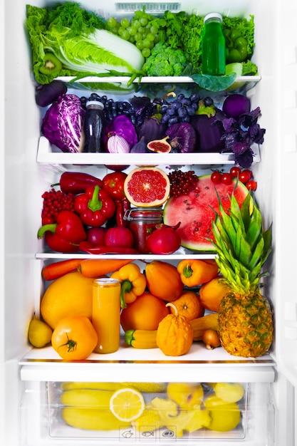 Verse biologische gezonde rauwe antioxidant violet, rood, groen, oranje en geel voedsel, groenten, fruit en sappen in veganistisch vegetarisch geopend volledige koelkast met vitamines. gezond eten dieet en levensstijl. Premium Foto