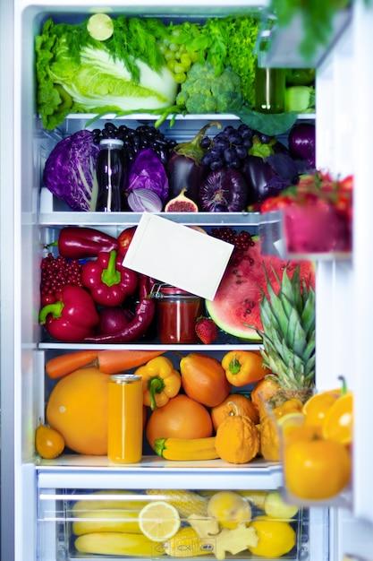 Verse biologische gezonde rauwe antioxidant violet, rood, groen, oranje en geel voedsel, groenten, fruit en sappen in veganistisch vegetarisch opende een volledige koelkast met vitamines met ruimte voor tekst. gezond eten. Premium Foto