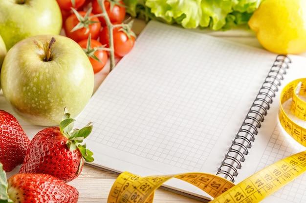 Verse biologische groenten en fruit, lege notitieblok openen en pen op houten Premium Foto