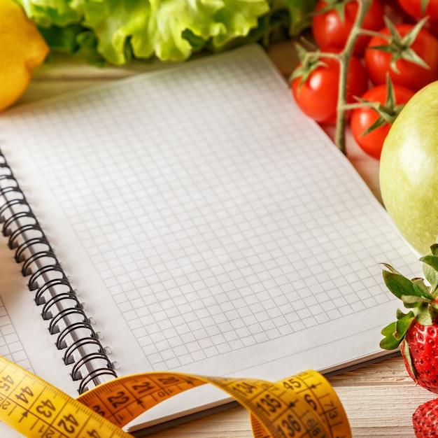 Verse biologische groenten en fruit, lege notitieblok openen en pen Premium Foto