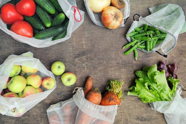 Verse biologische groenten, fruit en greens in herbruikbare gerecyclede gaaszakken. zero waste shopping concept. geen plastic voor eenmalig gebruik. Premium Foto