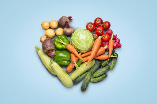 Verse biologische groenten op een blauwe ondergrond. concept van het kopen van boerderij groenten, zorg voor gezondheid, oogst. hart vorm. landelijke stijl, farm fair. plat lag, bovenaanzicht Premium Foto