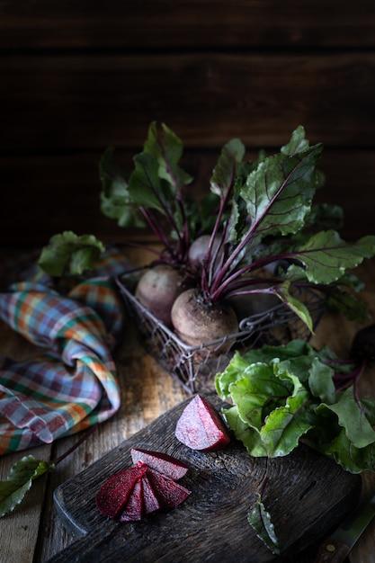 Verse biologische rode bieten met bladeren in een rieten mand op een houten tafel. natuurlijke biologische groenten. herfst oogst. rustieke landelijke stijl. Gratis Foto