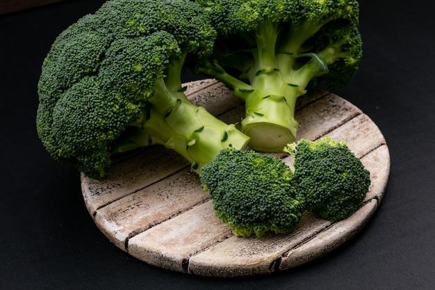 Verse broccoli op snijplank op zwarte ondergrond Gratis Foto
