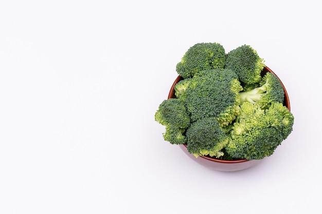 Verse broccolibos van groene broccoli in bruine ceramische die kom op witte oppervlakte wordt geïsoleerd Gratis Foto